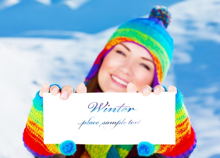 Picture of cute happy woman holding paper card with text in hands, pretty cheerful female having fun outdoors in wintertime, wearing stylish colorful winter hat and gloves, shallow depth of field photo