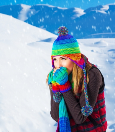 Picture of cute female in winter mountains, snowfall outdoors, beautiful woman wearing colorful wool hat, scarf and gloves, woman froze outdoor in cold snowy weather, wintertime holidays photo