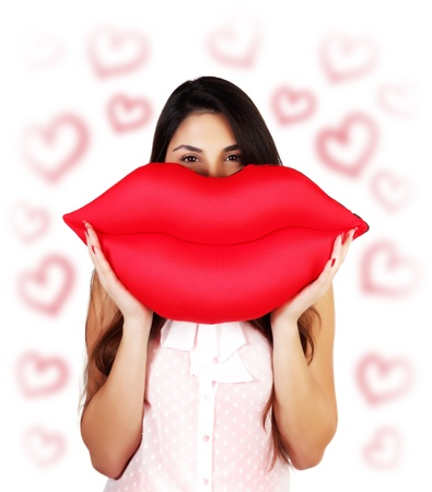 Photo of pretty brunette woman holding in hands big red lips, soft pillow-toy kiss-shaped, happy female having fun, isolated on white background with red heart shapes, Valentine day, love concept photo