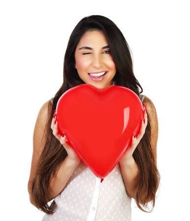 Image of cute brunette girl holding red balloon heart-shape in hands, portrait of happy woman isolated on white background, Valentine day, romantic gift, health care, medical treatment, love concept  photo