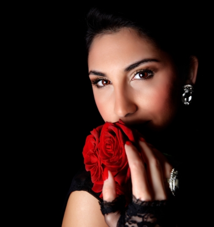 Picture of gorgeous woman holding beautiful red roses in hands isolated on black background, attractive arabic female with bouquet of romantic flowers, Valentines day, love concept