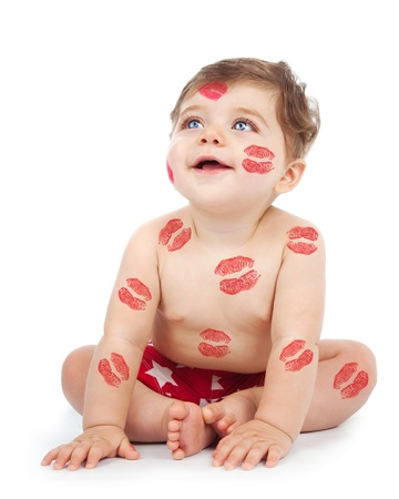 Photo of happy kid covered with red kisses print on the body, adorable baby boy sitting in studio isolated on white background, nice toddler looking up, Valentine day, love concept photo