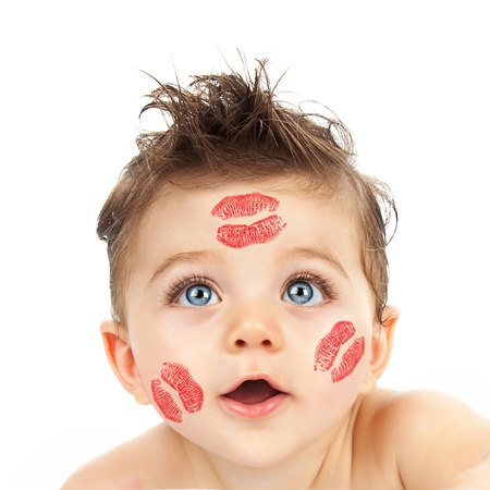 closeup portrait of pretty child with red kisses on his cheeks isolated on white background photo