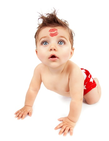 day care: Image of funny baby boy crawling in studio, happy child with red kiss on the forehead isolated on white background, Valentine day, romantic holiday, adorable kid, love and care concept