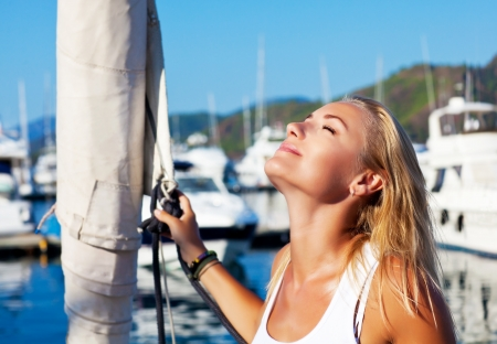 Beautiful woman sailing, young adult lady enjoying summer travel, close-up portrait on sexy female face, summer cruise holidays, European girl tourist traveling in sail boat around the world photo