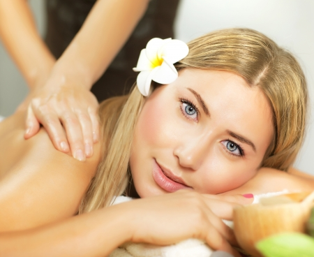dayspa: Photo of pretty woman enjoying day spa, cute female lying down on massage table, frangipani flower in hair, alternative treatment, natural cosmetics, luxury spa salon, health care and beauty concept