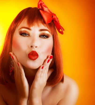 kissing lips: Picture of beautiful redhead girl with fashionable hairstyle and gorgeous red accessories isolated on orange background Stock Photo