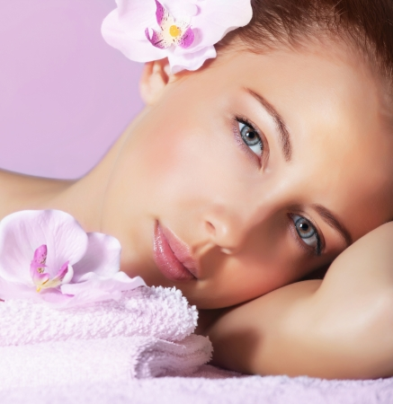 Image of cute young lady enjoying dayspa, closeup portrait of pretty woman with orchid flower in head on pink background, luxury spa resort, healthy lifestyle, beauty treatment and skin care concept photo