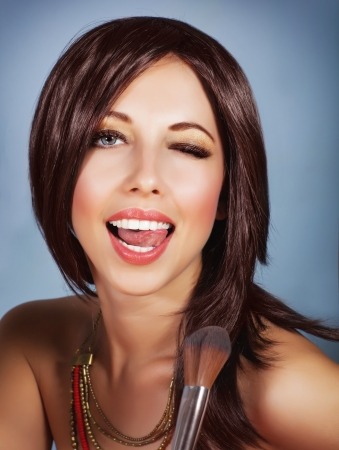 mouth closed: Photo of gorgeous female with perfect makeup isolated on blue background, sexy brunette woman holding in hand brush for blush, playful young lady with open mouth and closed one eyes, beauty concept