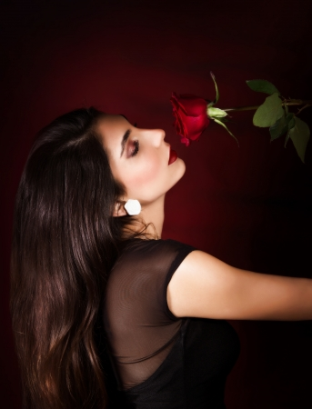 long red hair woman: Photo of beautiful woman with red rose, side view of gorgeous female with black long hair isolated on dark red background, closeup portrait of sexy girl with flower, Valentine day, passion concept Stock Photo