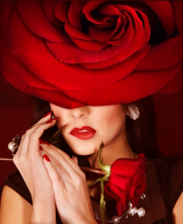 Picture of gorgeous woman wearing fashionable red roses hat, closeup portrait of brunette female with stylish makeup and flower on head, luxury beauty salon, Valentine day, style and fashion concept photo