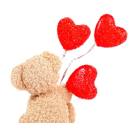 Photo of brown teddy bear holding red heart-shape balloons, rear view of sweet fluffy soft toy isolated on white background, romantic gift for Valentines day, cute present for love holiday Stock Photo - 17729739