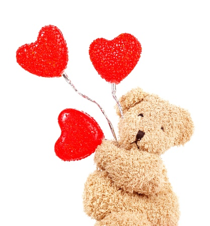 balloons teddy bear: Photo of brown teddy bear holding red heart-shape balloons, closeup portrait of sweet fluffy soft toy isolated on white background, romantic gift for Valentines day, cute present for love holiday