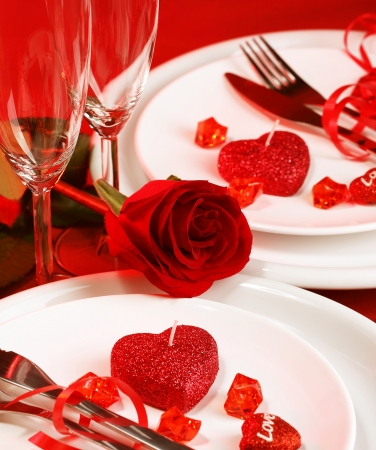 dinnerware:  beautiful romantic table setting, luxury white plates served with silverware and glasses for wine and decorated with red rose flower and heart-shaped candles, Valentine day, love concept