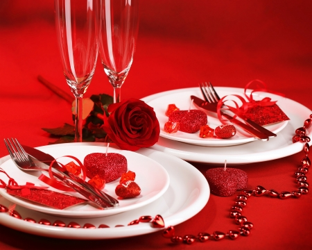 Photo of romantic dinner table setting, holiday banquet, white festive dinnerware on red tablecloth decorated with fresh rose flower and heart-shaped candles, Valentine day, two wineglasses photo