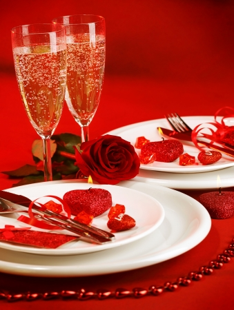 Picture of luxury table setting, romantic dinner, white festive utensil served with silverware and glasses for champagne, decorated with red rose flower and candles, Valentine day, love concept photo
