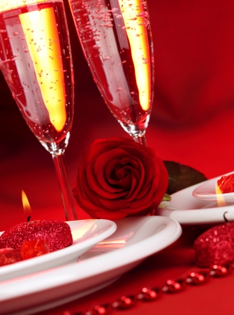 Image of beautiful Valentine day dinner still life, two glasses for champagne, alcohol beverage, romantic drink, sparkling wine, red rose and candle, festive table setting, love concept  photo