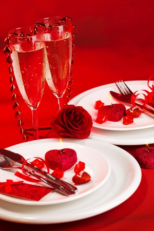 Picture of red holiday table decoration, white luxury dinnerware served with knife and fork, two glass for champagne, sparkling wine, romantic dinner, Valentines day, romance and love concept photo