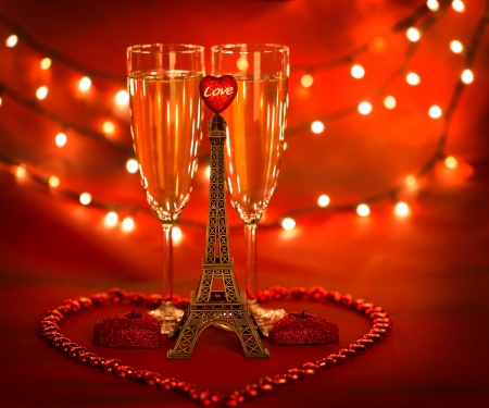 Picture of two glass with champagne decorated with little Eiffel tower and heart-shaped candles and beads on red background with glowing lights, honeymoon in Paris, romantic holiday, Valentines day photo