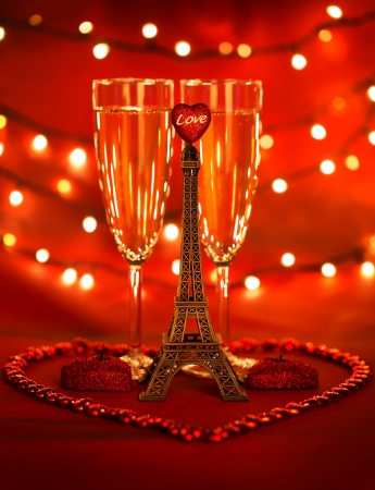 Image of two glass with romantic beverage, little eiffel tower with heart-shaped candles and beads decorated romantic table setting, honeymoon in Paris, festive lights in restaurant, Valentines day photo
