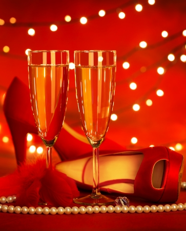anniversary sexy:  beautiful red romantic still life, two glass of champagne, shoe on high heels, luxury white pearl beads, fluffy feather, festive lights, holiday presents, Valentine day, love concept