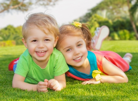 Picture of brother and sister having fun in the park, two cheerful child laying down on green grass, little girl and boy playing outdoors, best friends, happy family, love and happiness concept photo