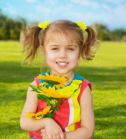 Picture of cute happy little girl wearing colorful dress and holding in hands beautiful sunflower bouquet, adorable small female in garden with fresh yellow flowers, sweet child having fun outdoor photo