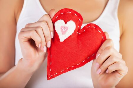 doctor holding gift: Picture of big red heart in hands, female holds handmade sewn soft toy, macro, shallow dof, woman with Valentine gift, conceptual image of health care or love Stock Photo
