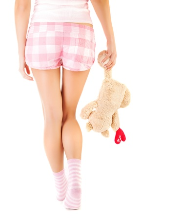 Conceptual image of one-sided love, rear view of woman wearing pink shorts and socks and holding teddy bear in hand, break up, broken heart, first unhappy love, sadness and loneliness concept photo