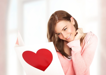Image of happy beautiful female reading romantic postcard with big red heart, attractive brunette woman got sensual greeting card and isolated on white background, Valentine day,love concept photo