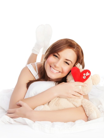 Picture of happy woman laying down in bed linen and enjoying romantic present, soft bear and red handmade heart-shape toy as gift for Valentines day holiday, isolated on white background, love concept photo