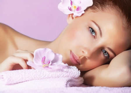Picture of cute female with pink orchid flower in head lying down on massage table, healthy lifestyle, luxury spa resort, enjoying dayspa, aroma therapy, pampering and skin care concept photo