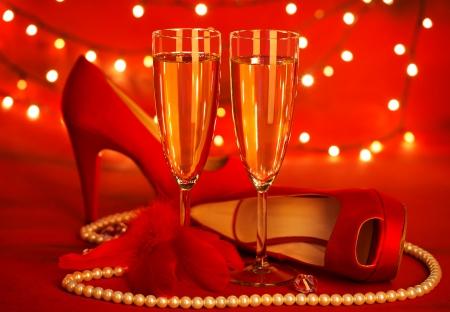 tacones rojos: Foto de la hermosa naturaleza muerta rojo romántico, dos copa de champán, zapatos de tacones altos, los granos de lujo blanco de perlas, plumas suaves, luces festivas, regalos de vacaciones, día de San Valentín, concepto de amor