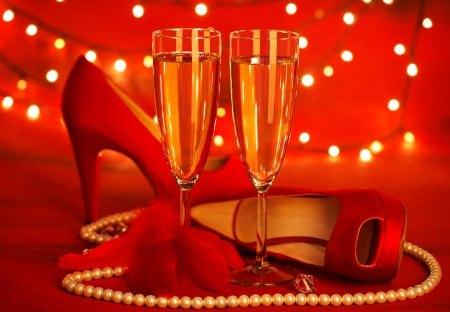 high life: Photo of beautiful red romantic still life, two glass of champagne, shoes on high heels, luxury white pearl beads, fluffy feather, festive lights, holiday presents, Valentine day, love concept