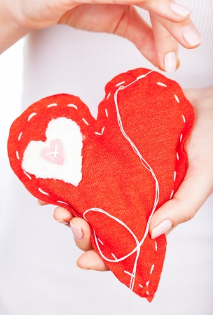 hands holding heart: Photo of red handmade heart-shaped soft toy, Valentine day, romantic relationship, cardiology hospital, medical help, healthy lifestyle, beautiful present, love and health care concept Stock Photo