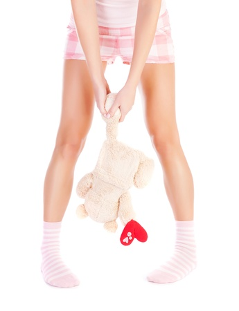 heartbroken: Conceptual image of one-sided love, front view of woman wearing pink pajamas, girl holding bear in hands, break up, heartbroken female, first unhappy love, sadness and loneliness concept Stock Photo