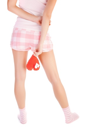 Picture of young woman holds red heart soft toy, body rear view isolated on white background, female legs, lonely heartbroken girl wearing pajamas, one-sided love and parting in relationship concept photo