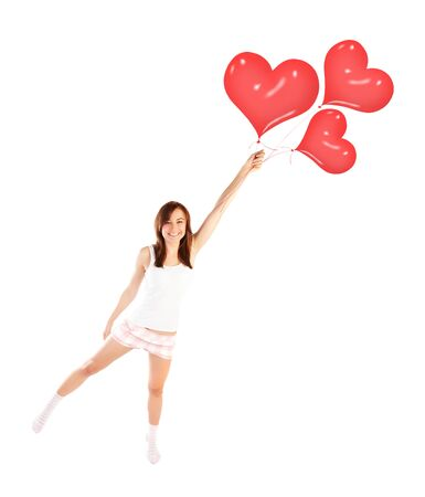 Image of cute female flying on red heart-shaped balloons, laughing woman isolated on white background, freedom lifestyle, Valentine day, romantic dream, first affection, love and happiness concept photo