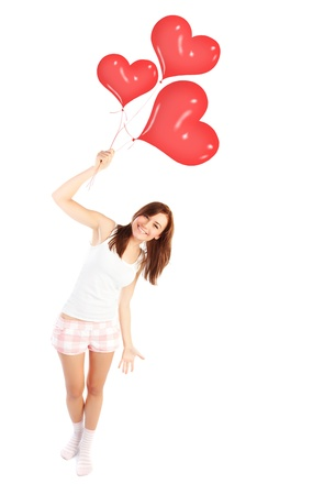Image of a cute happy girl holding red heart balloons, fit woman smiling isolated on white background, freedom lifestyle, weight loss concept, romantic wish on Valentine day, love happiness and health photo