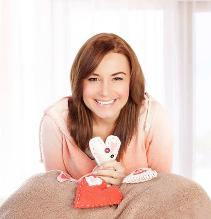 Photo of beautiful happy female sitting at home in bedroom with cute handmade hearts soft toy, symbol of love, romantic gift, Valentine day, present for holiday, affection and happiness concept photo