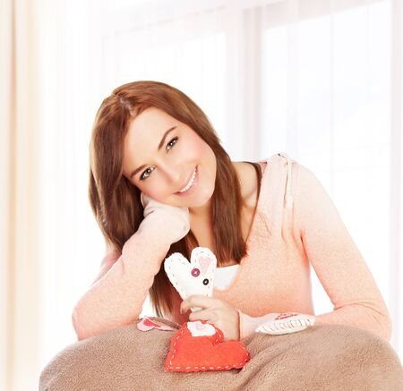 Picture of attractive brunette woman at home enjoying gift, cute girl sitting on bed and holding in hand beautiful white heart-shaped soft toy, handmade present, romantic holiday, Valentines day Stock Photo - 17641638
