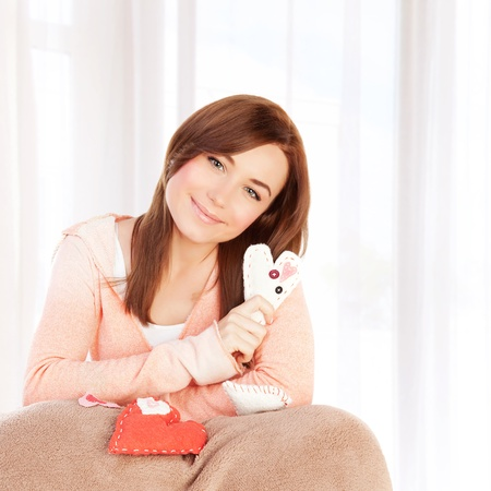 Image of beautiful woman sitting on the bed at home and covered with blanket holding handmade sew heart, Valentine day, romantic gift, lovely female, 14 of february, love and happiness concept photo