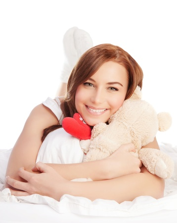 Picture of happy woman laying down in the bed, girl enjoying romantic present, soft bear and red handmade heart-shape toy as gift for Valentines day holiday, isolated on white background, love concept photo