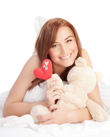 Picture of happy woman laying down in the bed, girl enjoying romantic present, soft bear and red handmade heart-shape toy as gift for Valentines day holiday, isolated on white background, love concept Stock Photo - 17641639