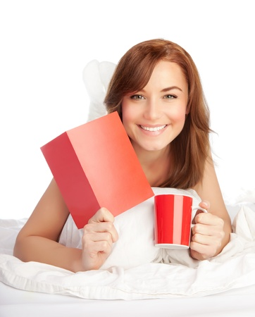 Happy woman laying down in the bed, girl got romantic Valentine greeting card present, drinking coffee on holiday morning, female relaxing at home, isolated on white background, love concept photo
