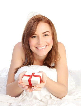 Picture of a happy young woman with gift box, cheerful female relaxing, laying down in the bed, isolated on white background, pretty girl portrait with romantic present, holiday celebrations concept photo