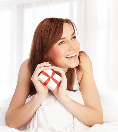 Photo of cute woman enjoying gift, closeup portrait of pretty female at home holding in hands little white present box with red ribbon, Valentine day, romantic holiday, love concept photo