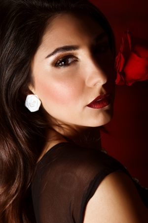 Photo of beautiful brunette woman with red rose isolated on dark background, closeup portrait of gorgeous female with perfect makeup, luxury beauty salon, Valentine day, passion and elegance concept photo