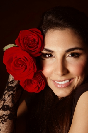 Picture of attractive female with beautiful red roses isolated on black background, sexy arabic girl with cute romantic gift, Valentines day, perfect makeup, glamorous woman, elegance concept Stock Photo - 17792513
