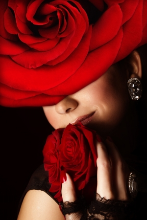 Photo of pretty arabic woman wearing stylish red floral hat, closeup portrait of attractive female with fresh roses bouquet, romantic gift for Valentine day holiday, beauty salon, fashion concept photo